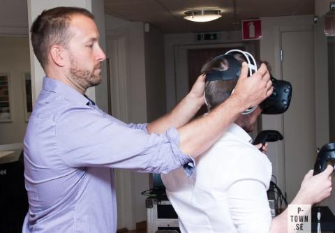 VR-specialisten Mikael Wahlberg visar hur hörlurarna ska sitta på Gustav Pekkari.