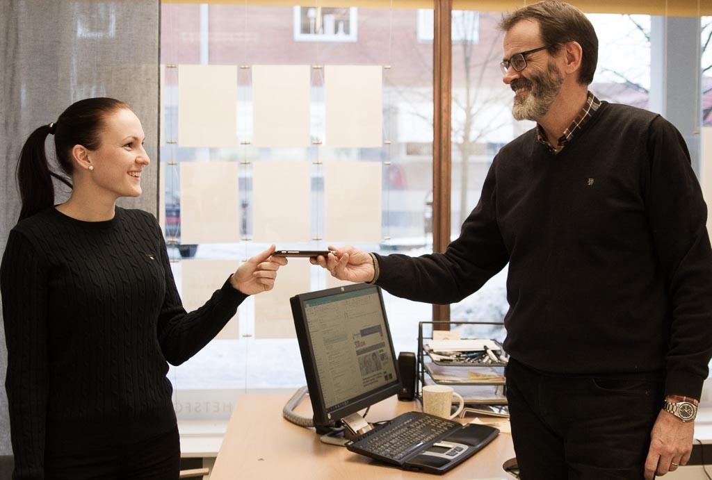 """Per Lundgren lämnar över stafettpinnen (telefonen) till den nya mäklaren Frida Risberg. """"Var dig själv!"""" är hans råd till henne."""